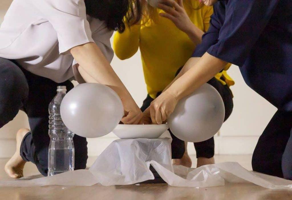 Détail de ballons de baudruche soufflant dans l'eau contenue à l'intérieur d'une assiette