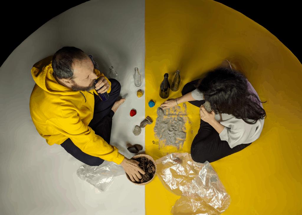 deux artistes assis dans un cercle font une performance à partir d'objets sonores