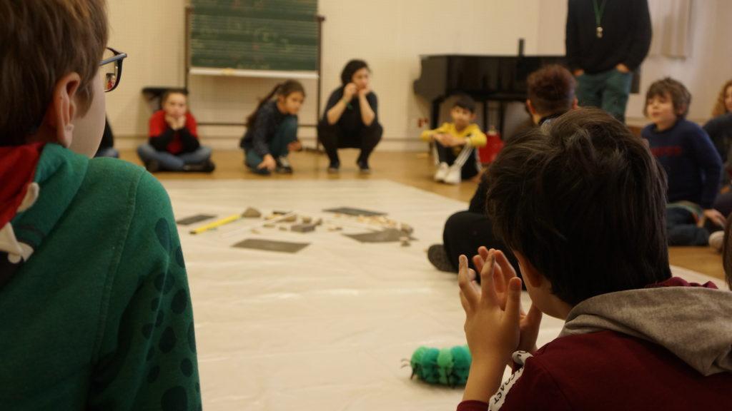 deux enfants, de dos, observent des objets sonores placés au centre d'un groupe d'élèves